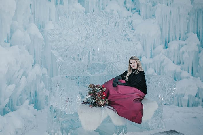 Engagement photos at the edmonton ice castles with a bridal bouquet of red tulips and burgundy flowers
