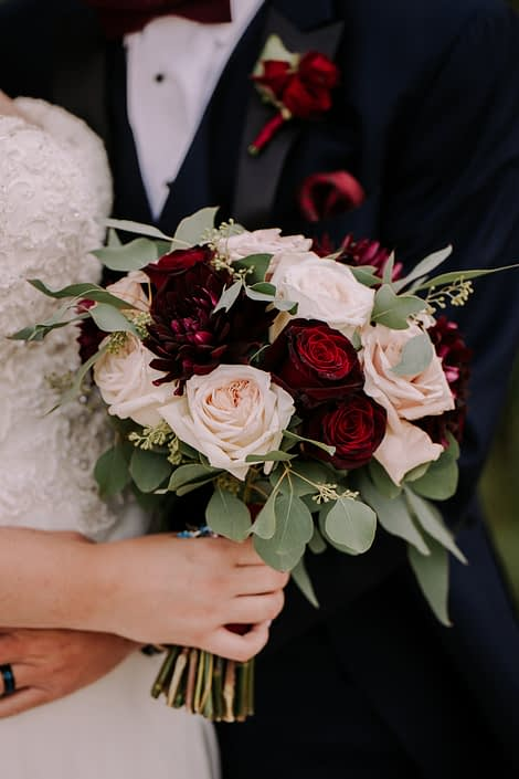 Burgundy and Blush bridal bouquet featuring dalias, quicksand roses, black baccara roses, white o'hara garden roses, and eucalyptus; burgundy rose boutonniere.