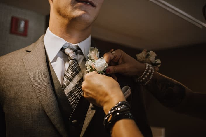 mother pinning on the grooms boutonniere of white spray rose and pale pink astilbe