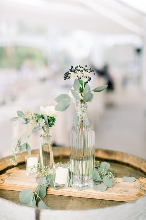 Bud vases for Kayla and Joel's Timeless White wedding filled with white tibet roses, berries, and fresh eucalyptus.