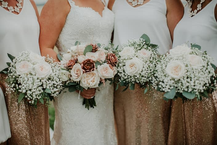 Bride and bridesmaids in rose gold sequin bridesmaid dresses with bouquets of rose gold succulents babies breath and white ohara garden roses