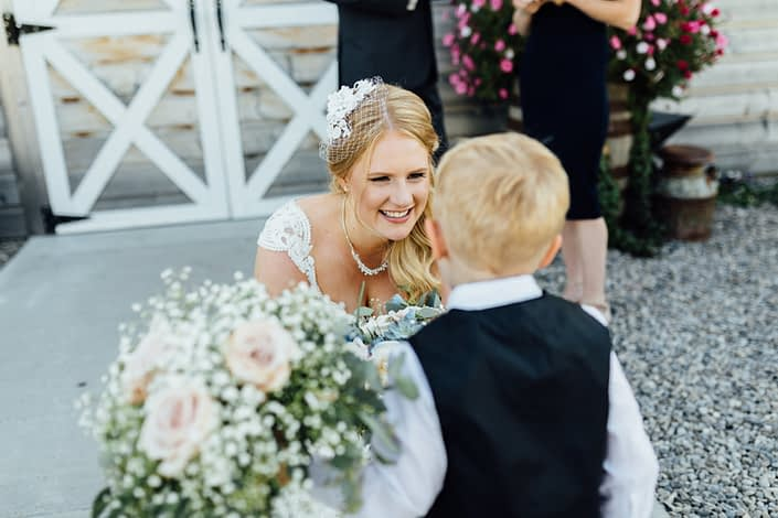 Bride and ring bearer with bouquet made of quicksand roses and babies breath with eucalyptus greenery.