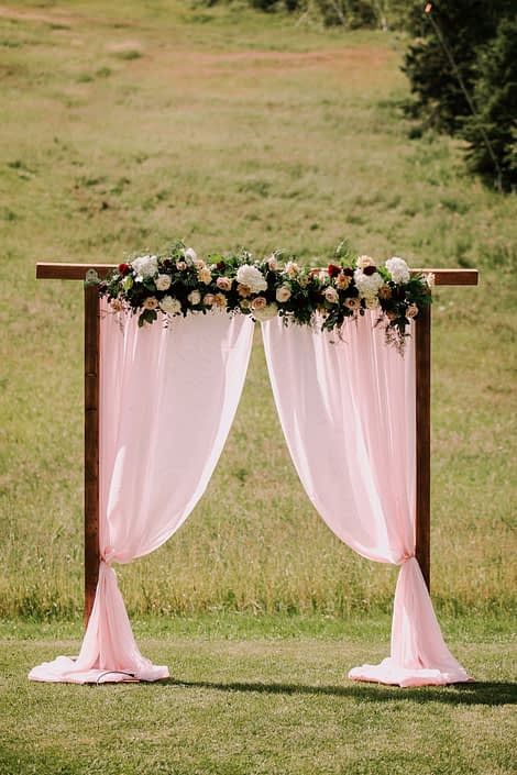 Rustic Chic Burgundy and Blush Archway Arrangement designed with Avignon Chrysanthemum, white o'hara garden roses, white hydrangeas, quicksand roses, salal and eucalyptus.