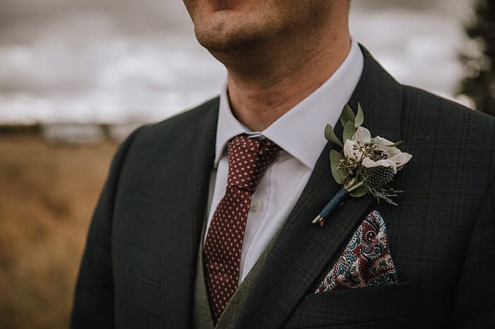Groom with panda anemone and anenome boutonniere wrapped with navy silk ribbon
