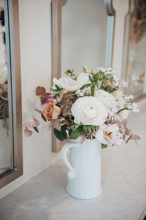 Floral arrangement in a jug designed with roses, ranunculus, alyssum, and rose gold painted plumosa and eucaluptus greenery