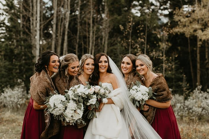 Brittany and her bridesmaids wearing fur shawls and holding white bouquets; bridesmaids bouquets were designed with hydrangeas and eucalyptus; bride's bouquet designed with white o'hara garden roses, quicksand roses, white ranunculus, lisianthus, burgundy astrantia and eucalyptus greenery