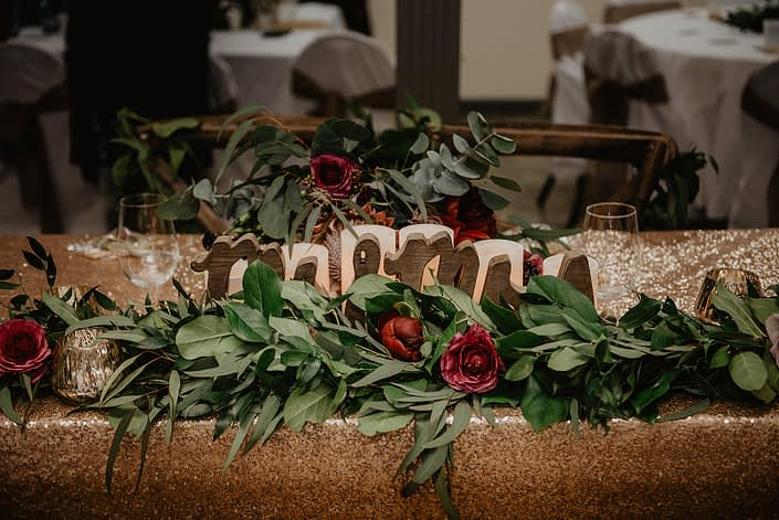 Rustic Boho Chic Wedding - Mr and Mrs sign with a long garland made of fresh greenery and red flowers on a gold sequin covered head table.
