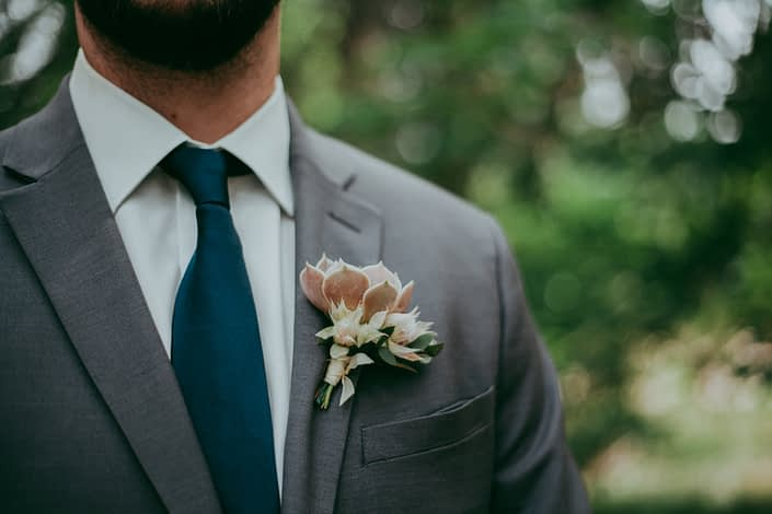 Groom in charcoal suit with navy tie wearing boutonniere of blush lola succulent and blushing bride protea with silk ribbon tie