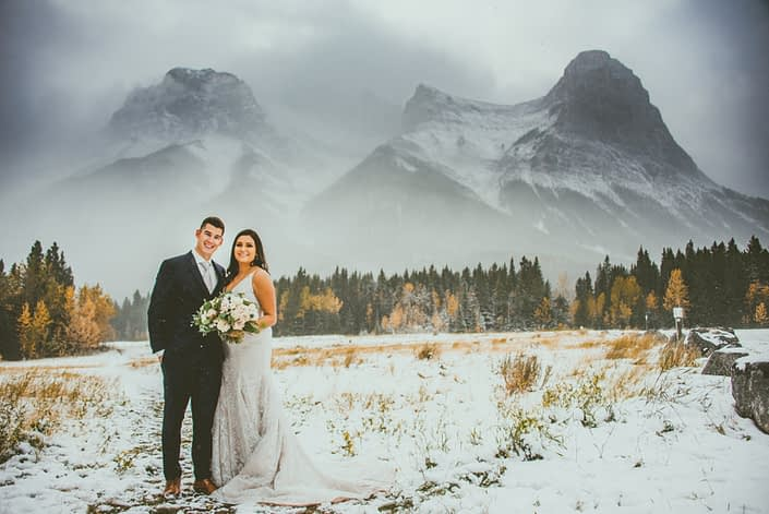 Blush and Mauve Canmore Wedding - Bride and groom standing in a snowy field in the Rocky Mountains near Canmore. Bride is carrying a blush, white and mauve bouquet.