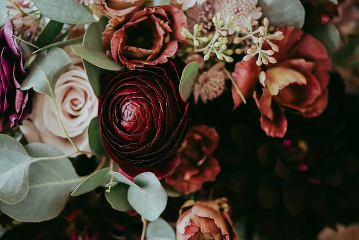 Rustic burgundy and dusty rose wedding flowers close up; ranunculus, lisianthus, quicksand roses, astrantia and seeded eucalyptus