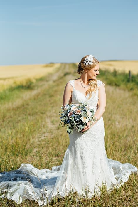 Bride standing by a field of wheat holding a blush and blue bridal bouquet featuring quicksand roses, white o'hara garden roses, blue delphinium, gypsophila (babies breath) and a mixed variety of eucalyptus.