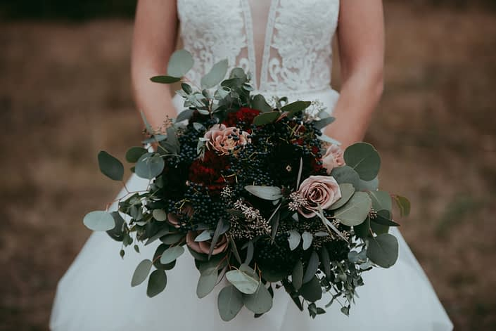 bouquet shot close up of bride bouquet with amnesia roses, viburnum berries in navy red roses and burgundy dahlias and mixed eucalyptus greenery bride gown with plunging neck and lace