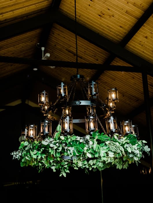 Chandelier at Canyon Ski Resort adorned with lush fresh greenery including salal, monstera leaves and eucalyptus greenery.