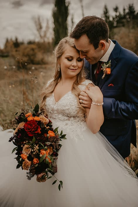 Bride and groom, Haley and James, rustic fall wedding bridal bouquet and boutonniere; bouquet made of chocolate cosmos, burgundy dahlias, hearts garden roses, orange hypericum, golden mustard roses, orange spray roses, italian ruscus and seeded eucalyptus; boutonniere made of orange spray rose, solidago, hypericum, italian ruscus and eucalyptus.
