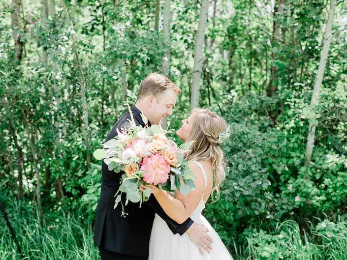 Taylor and Griffin smiling at each other holding lush and modern bouquet featuring coral charm peonies, quicksand roses, golden mustard roses, astilbe, astrantia, cappuccino roses, monstera leaves, eucalyptus and boston fern.