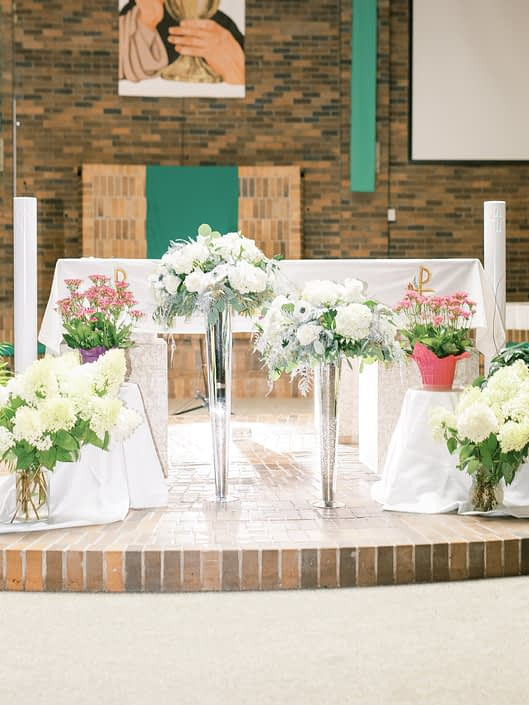Ceremony alter arrangements designed atop tall silver mercury glass vases with white flowers