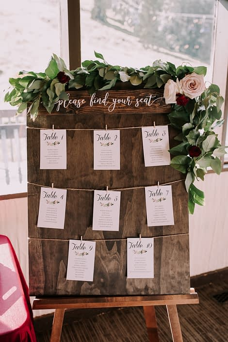 Seating chart sign with fresh greenery garland accented by burgundy and blush flowers.