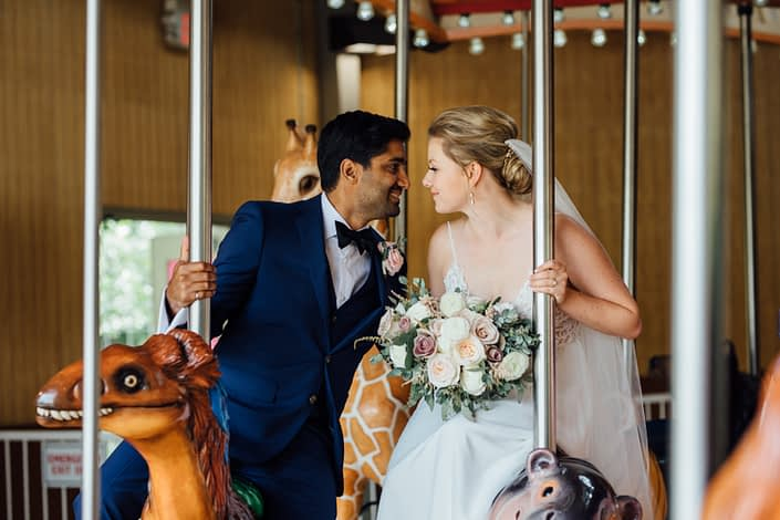 Bride and groom, Jill and Jason, on a carousel at the Calgary Zoo; bride holding romantic blush bouquet featuring white o'hara garden roses, white ranunculus, quicksand roses, light pink astilbe and eucalyptus greenery.