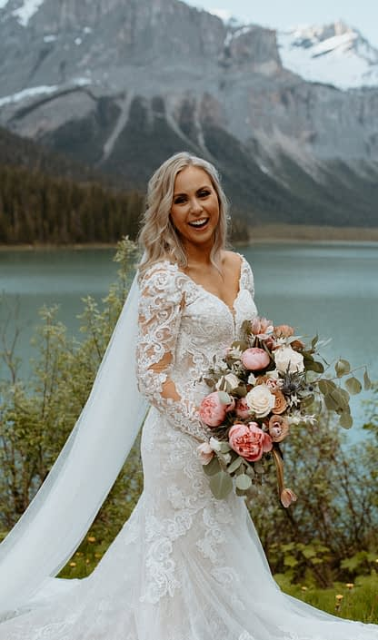 Bride and bridal bouquet designed with pink tulips, white roses, toffee roses, tulips, blue eryngium, bleached italian ruscus and eucalyptus greenery