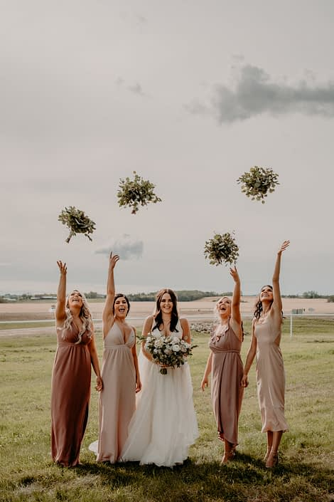 The bride is holding a blush, ivory and white bouquet while her bridesmaids are throwing their fresh mixed eucalyptus bouquets in the air.