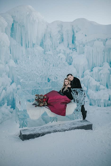 Ice couch at the edmonton ice castles for an engagement photoshoot with a bridal bouquet