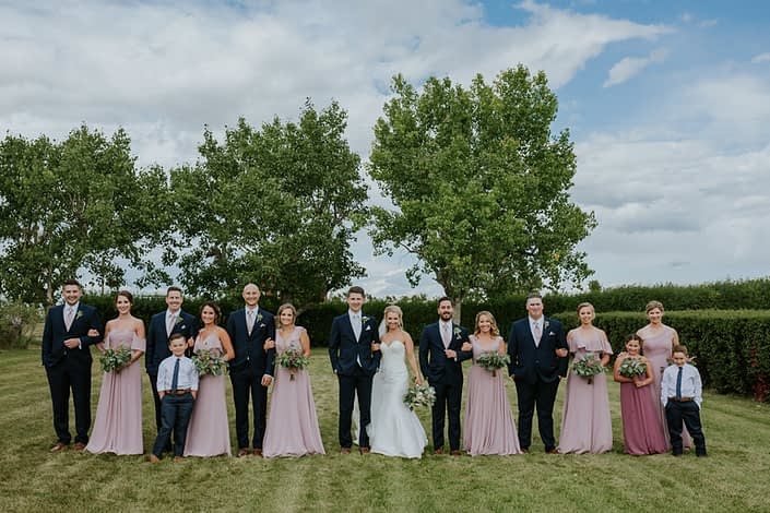 Brooke and Levi's Rustic Chic Blush Wedding party walking towards camera.
