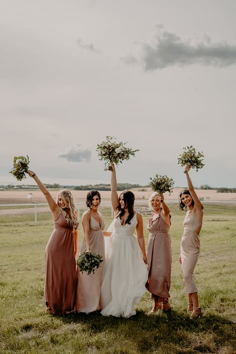 Bride and bridesmaids having fun and holding their bouquet in the air. The bridesmaids are wearing mauve dresses and carrying fresh mixed eucalyptus bouquets and Erika is wearing a white bridal gown and holding a blush, ivory and white bouquet with eucalyptus greenery.