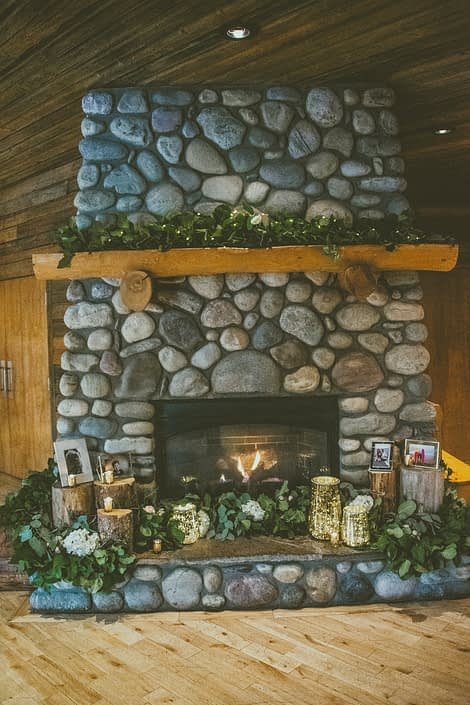 Cozy stone fireplace at the Cornerstone Theatre in Canmore, Alberta decorated with fresh greenery and white hydrangea garlands, candles, and photographs.