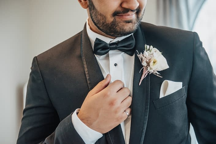 Blush boutonniere and black tuxedo with bow tie
