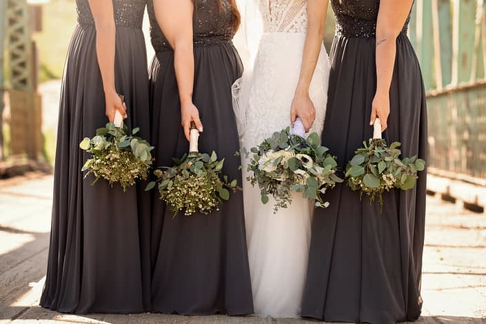 Bride and bridesmaids with bouquets facing down