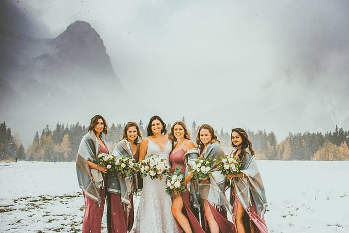 Meagan and her bridesmaids standing in a snowy field in the Rocky Mountains. The bridesmaids are wearing mauve dresses and blanket scarves. They are all carrying mauve, blush and white bouquets with greenery. Blush and Mauve Canmore Wedding.