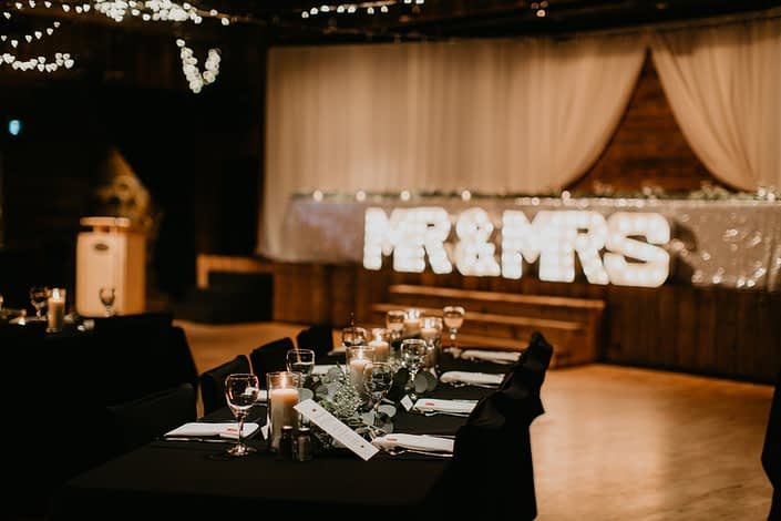Reception tables decorated with candles, eucalyptus and babies breath with black table cloths and white napkins