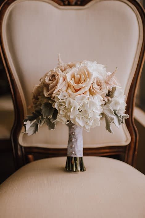 antique chair with bridal bouquet made with white hydrangea and blush quicksand roses and dusty miller