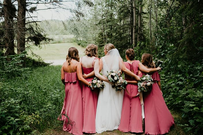Bride walking with bridesmaids wearing pink berry coloured dresses; holding bouquets designed with burgundy dahlias, white ranunculus, roses, astilbe, scabiosa and eucalyptus greenery.