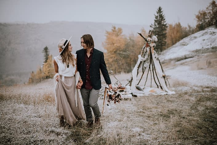 Couple walking near a tee pee for a neutral fall styled shoot