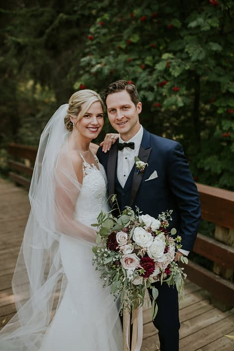 bride and groom on a bridge in the forest for s summer wedding holding a bridal bouquet designed with burgundy dahlia and blush and white roses and eucalyptus greenery