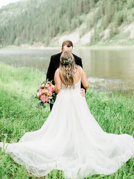 Bride kissing groom; she has a hair piece made of greenery and is holding a modern coral charm peony bouquet with golden mustard yellow rose accents finished with eucalyptus greenery and boston fern.