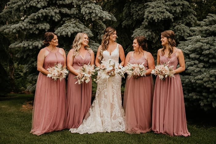 Bride and bridesmaids wearing dusty mauve with rustic boho bouquets designed with quicksand roses, amnesia roses, blush ranunculus, phalenopsis orchids, light pink astilbe, bleached bracken fern, bunny tail, eucalyptus cinerea, and olive branches