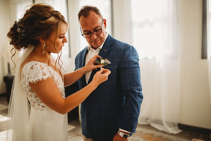 Bride pinning white and blue boutonniere onto Father of the Bride.