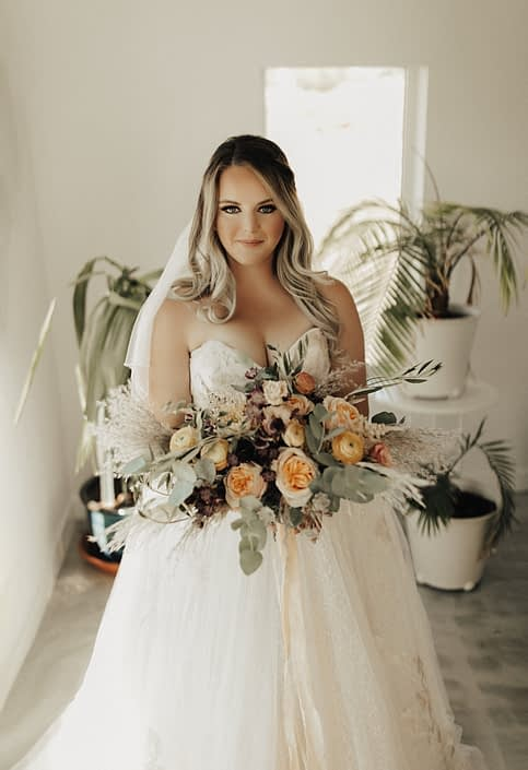 Bride with boho bridal bouquet designed in peach and burgundy tones with flowers such as Juliet Garden roses, dahlias, ranunculus, pampas grass and olive branches