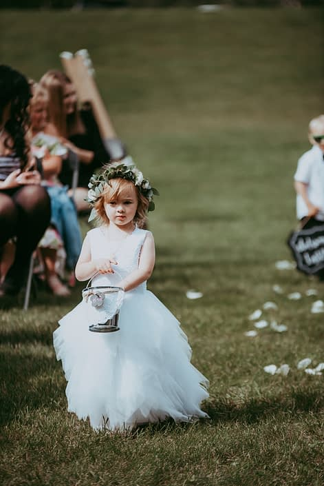 Flower girl wearing white and green flower crown and dropping flower petals