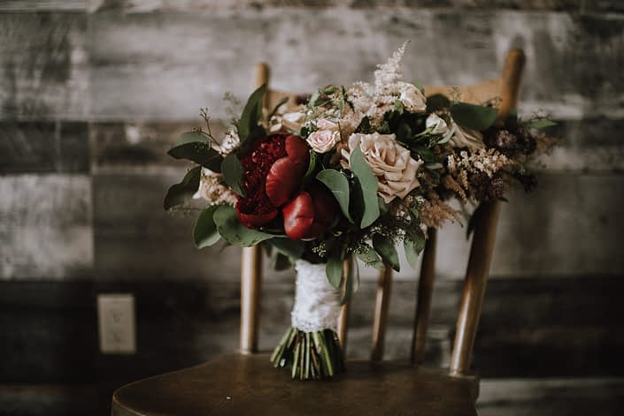Rustic Red and Blush bridal bouquet on wooden chair designed with red charm peony, quicksand roses, bombastic spray roses, light pink astilbe, burgundy astrantia and eucalyptus greenery. The handle is wrapped with a blush satin with lace overlay.