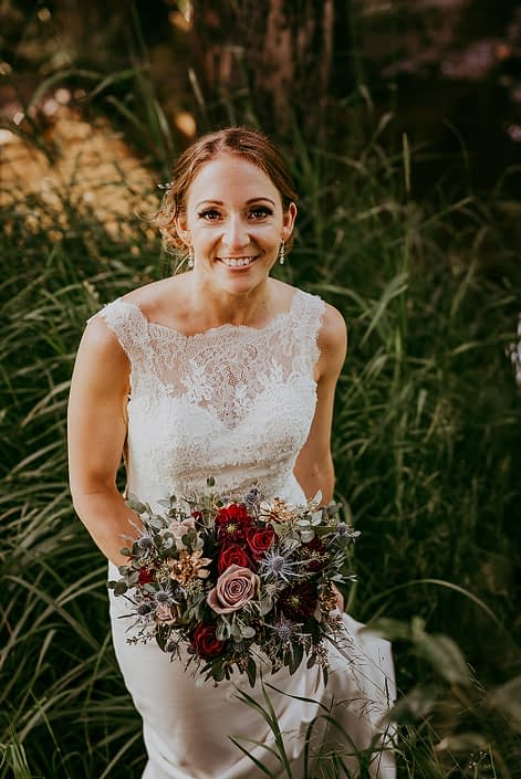 bride Tanya and bridal bouquet designed with amnesia roses, black baccara roses, burgundy dahlias, navy eryngium, rose gold painted succulents and eucalyptus greenery