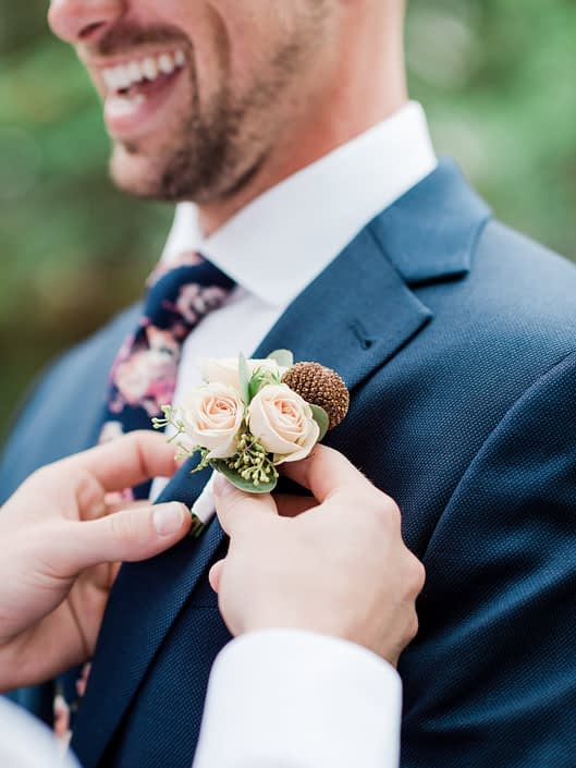 Groom getting his dusty rose boutonniere attached.