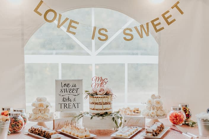 Dessert table set with naked cake and rose gold accents with candy bar and small desserts and love is sweet banner