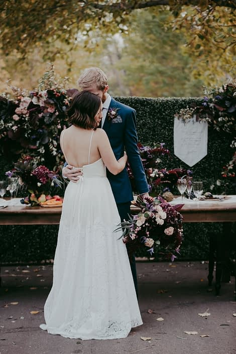 bride and groom in front of a boxwood backdrop with florals in burgundy and blush