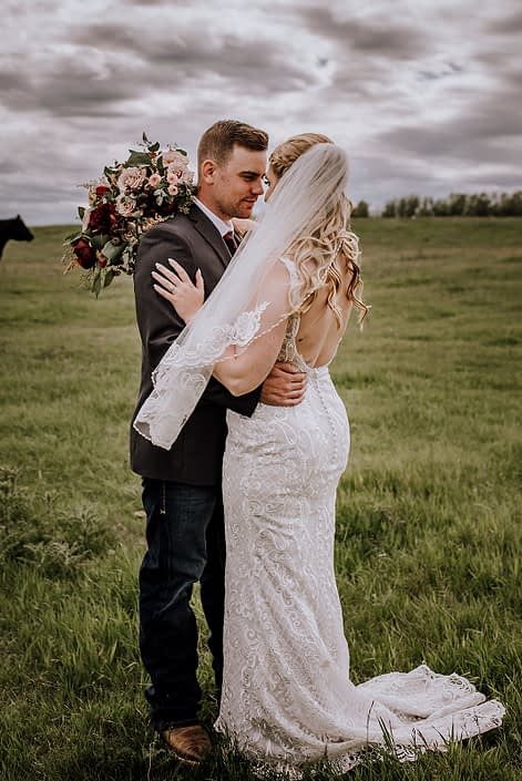 Bride and groom standing in a field with rustic red and blush bridal bouquet featuring red charm peonies, quicksand roses, blush spray roses, burgundy astrantia, light pink astilbe, and eucalyptus greenery.