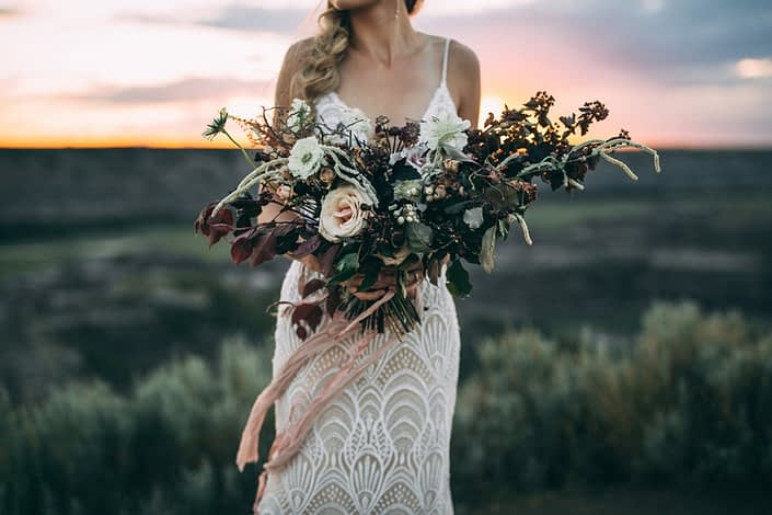 bride holding bridal bouquet designed with roses, amaranthus, scabiosa and burgundy greenery