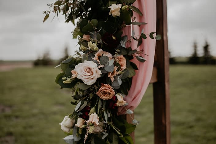 Archway garland for Crystal and Chance's Sweet Haven Barn Wedding designed with light pink astilbe, burgundy dahlias, cappuccino roses, quicksand roses, salal and eucalyptus.