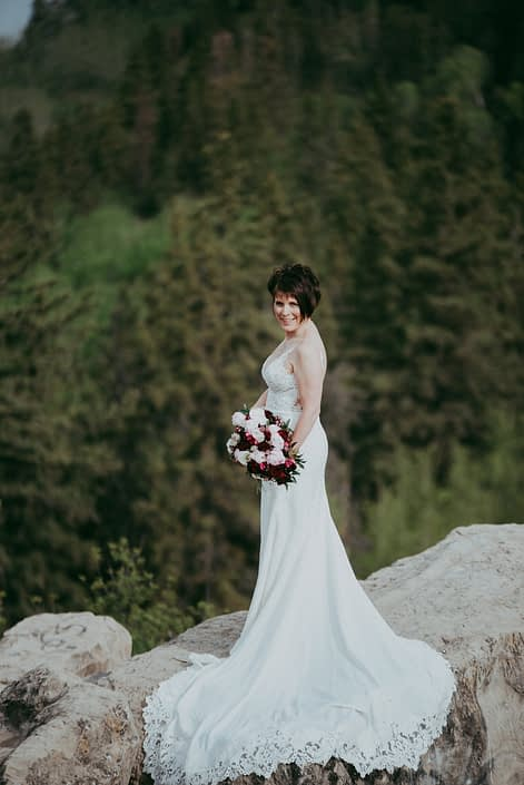 Sandra holding her pink and burgundy bridal bouquet featuring burgundy helleborus, Sarah Bernhardt peonies, blush and white ranunculus, black baccara roses, blackberry scoop scabiosa, burgundy tulips and pale pink astrantia with eucalyptus greenery.